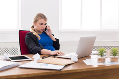 Pregnant business lady at work talking on phone Stock Photos