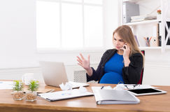 Pregnant business lady at work talking on phone Stock Image