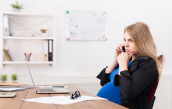 Pregnant business lady at work talking on phone Royalty Free Stock Photography
