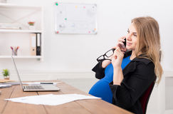 Pregnant business lady at work talking on phone Royalty Free Stock Photos