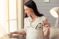 Pregnant business woman with gadget Stock Photo