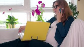 Pregnant business woman with phone thumbing binder with documents papers. Static shot. 4K UHD stock video footage