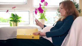 Pregnant business woman with tablet computer and binder files working at home. Pregnant business woman with tablet computer and binder files working sitting on stock video footage