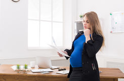 Pregnant business woman talking on phone at office Stock Image