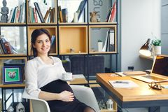 Pregnant business woman working at office motherhood sitting holding belly royalty free stock images