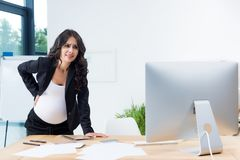 pregnant businesswoman with back pain at workplace looking stock image