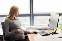Pregnant businesswoman with computer at office Royalty Free Stock Images