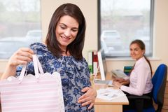 Pregnant Businesswoman Going On Maternity Leave From Office. With Gift royalty free stock photo