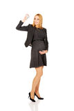 Pregnant businesswoman holding plane model Stock Photography