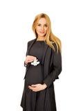 Pregnant businesswoman holding plane model Stock Photography