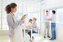 Pregnant businesswoman reading file with team behind her Royalty Free Stock Photography