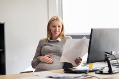 Pregnant businesswoman reading papers at office Stock Photography