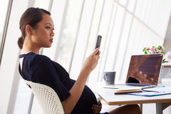 Pregnant Businesswoman Reading Text Message In Office Royalty Free Stock Photography