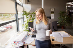 Pregnant businesswoman with smartphone at office Royalty Free Stock Photos