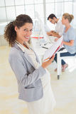 Pregnant businesswoman smiling at camera with team behind her Royalty Free Stock Images