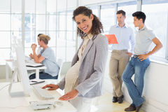 Pregnant businesswoman smiling at camera with team behind her Stock Photos