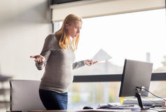 Pregnant businesswoman stressing at office work Royalty Free Stock Photos