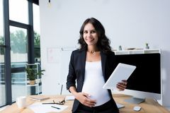 pregnant businesswoman with tablet at modern office looking stock photos