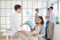 Pregnant businesswoman talking with colleague sitting at desk Stock Photos