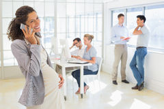Pregnant businesswoman talking on phone with team behind her Royalty Free Stock Photo