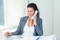 Pregnant businesswoman talking on phone while working on laptop Royalty Free Stock Images