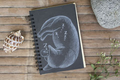 Pregnant cat sleeps hand-drawn illustration. Cat by white chalk on black paper. Black paper notepad on wooden background. Vintage wooden table with artwork Stock Photography