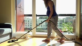 Pregnant caucasian house wife cleaning wooden floor with vacuum cleaner at home. Static shot. 4K UHD stock footage