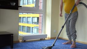 Pregnant caucasian woman relax on floor and hoover floor with vacuum cleaner stock video