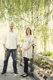 Pregnant couple. Attractive caucasian pregnant woman holding hands with husband standing in beautiful park smiling looking into camera Royalty Free Stock Photography