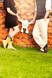 Pregnant couple. Expecting couple with eight months pregnant women wearing a black dress standing against a brick wall and holding a toy bear in the park Stock Photo