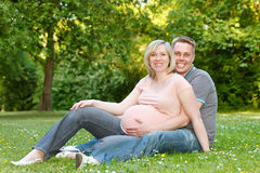 Pregnant couple. Resting in the park stock images