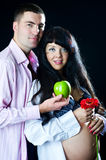 Pregnant couple with apple and flower Royalty Free Stock Photography