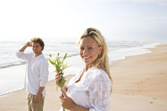 Pregnant couple on beach holding white flower Royalty Free Stock Photos