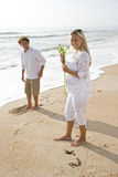 Pregnant couple on beach holding white flower Royalty Free Stock Photo