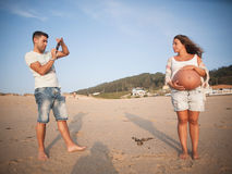 Pregnant couple in the beach Stock Image
