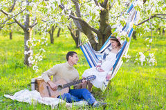 Pregnant couple in blooming garden at the picnic Royalty Free Stock Photography