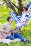 Pregnant couple in blooming garden at the picnic. Lazy time Stock Images