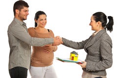 Pregnant couple buying new house. Pregnant women and her husband  buying new house and shaking hand with real estate agent women isolated on white background Royalty Free Stock Photography