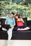 Pregnant couple chatting on sofa Royalty Free Stock Photo