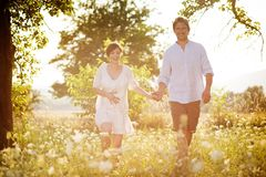 Pregnant couple. Happy and young pregnant couple hugging in nature royalty free stock photo