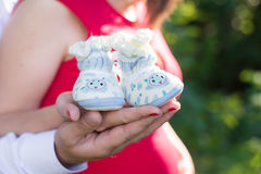 Pregnant couple holding hands in booties. Pregnant couple holding knitted blue and white booties on the background of the tummy Royalty Free Stock Images