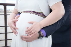 Pregnant couple holding hands on tummy. Pregnant couple with tenderness and love holding hands on her tummy against a white dress Royalty Free Stock Images