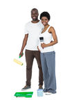 Pregnant couple holding roller paint and paint brush Stock Images