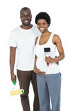 Pregnant couple holding roller paint and paint brush Royalty Free Stock Photos