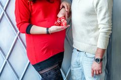 Pregnant couple holding shoes in hands stock photos