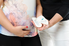 Pregnant couple holding socks Stock Photos