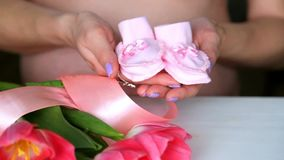 Pregnant couple holding tiny pink childs socks in hands. pregnant woman stock video footage