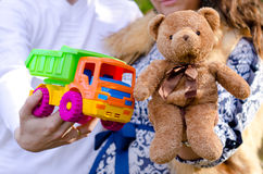 Pregnant couple holding a toy. Bear brown and bright toy car Royalty Free Stock Photos
