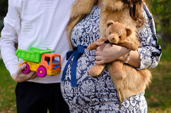 Pregnant couple holding a toy. Bear brown and bright toy car Stock Image