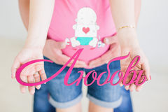 Pregnant couple holding wooden decorative letters Stock Images